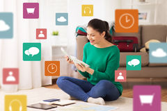 Happy woman with money and travel map at home. Tourism, travel, finances and people concept - happy young woman with money, tablet pc computer and map at home Royalty Free Stock Image