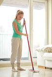 Happy woman with mop cleaning floor at home. People, housework and housekeeping concept - happy woman with mop cleaning floor at home stock photo