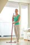 Happy woman with mop cleaning floor at home Stock Photography