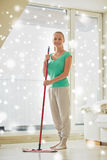 Happy woman with mop cleaning floor at home Royalty Free Stock Photos