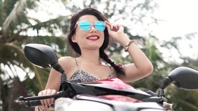 Happy woman on motorbike looking to the camera stock video