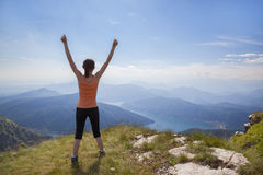 Happy woman on mountain top. Joyful girl standing on mountain top with raised arms looking at mountain landscape and blue sky Stock Photography