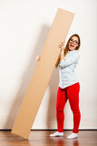 Happy woman moving into apartment carrying box. Stock Images