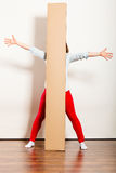 Happy woman moving into apartment carrying box. Royalty Free Stock Photo