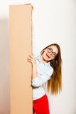 Happy woman moving into apartment carrying box. Stock Photos