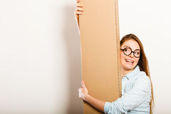 Happy woman moving into apartment carrying box. Royalty Free Stock Images