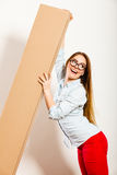 Happy woman moving into apartment carrying box. Royalty Free Stock Photography