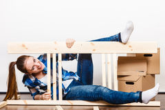 Happy woman moving in assembly furniture at home. Stock Photos