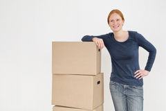 Happy Woman with Moving Boxes. A happy young woman leaning on a stack of moving boxes and smiling Royalty Free Stock Photography