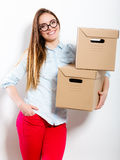 Happy woman moving into house carrying boxes. Royalty Free Stock Image