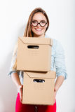 Happy woman moving into house carrying boxes. Stock Photography