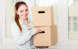 Happy woman moving into house carrying boxes. Royalty Free Stock Images