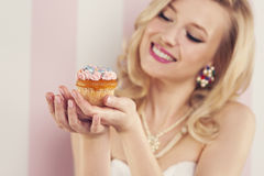 Happy woman with muffin. Smiling blonde woman holding small muffin Royalty Free Stock Photos