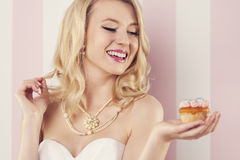 Happy woman with muffin. Smiling young woman holding pink muffin Stock Photos