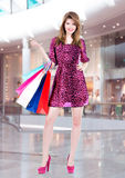 Happy woman with multicolor shopping bags in the mall Stock Images