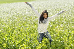 Happy woman in nature with outstretched arms in a flower field Stock Photo