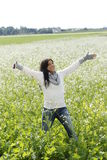 Happy woman in nature with outstretched arms in a flower field Stock Images
