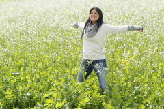 Happy woman in nature with outstretched arms in a flower field Royalty Free Stock Photo