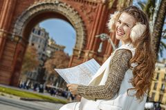 Happy woman near Arc de Triomf in Barcelona, Spain with map. In Barcelona for a perfect winter. Portrait of happy modern woman in earmuffs near Arc de Triomf in Royalty Free Stock Photo