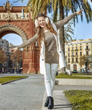 Happy woman near Arc de Triomf walking on parapet in Barcelona. In Barcelona for a perfect winter. Full length portrait of happy young woman in earmuffs near Arc Stock Photography