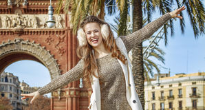 Happy woman near Arc de Triomf walking on parapet in Barcelona Royalty Free Stock Photo