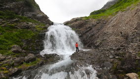Happy woman near beautiful waterfall in mountain. KAMCHATKA PENINSULA, RUSSIA - July 29, 2016: Happy woman tourist near beautiful waterfall in Mountain Range stock video footage