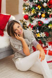 Happy woman near Christmas tree having phone call Royalty Free Stock Image