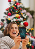 Happy woman near Christmas tree making self photo Stock Images