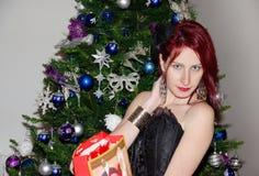 Happy woman near a Christmas tree Stock Photos