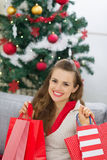 Happy woman near Christmas tree with shopping bags Stock Images