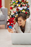 Happy woman near Christmas tree shopping online Stock Image