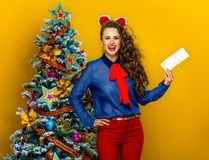 Happy woman near Christmas tree showing flight tickets. Festive season. happy modern woman near Christmas tree isolated on yellow background showing flight Royalty Free Stock Images