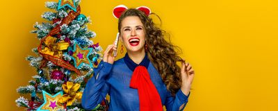 Happy woman near Christmas tree talking on a mobile phone Stock Image