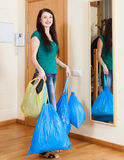 Happy  woman near door with garbage Royalty Free Stock Image