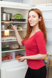 Happy  woman near opened refrigerator Stockbilder