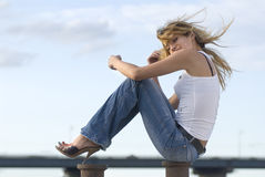 Happy woman near a river. Beautiful happy blond woman near a river in jeans Royalty Free Stock Image