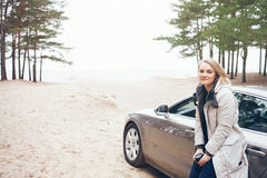 Happy woman next to car, relaxing on road trip adventure travel. Royalty Free Stock Photo