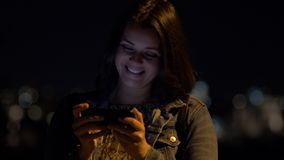 Happy woman at night in city texting message with cell phone. With lights stock video footage