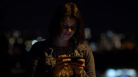 Happy woman at night in city texting message with cell phone. With lights stock footage
