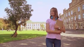 Happy woman with notebook walks in campus area. Smiling blonde student with headphones holding notebooks near university. girl with blond hair wearing pink t stock footage
