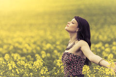 Happy woman in ocean of yellow flowers. Attractive genuine young girl enjoying the warm summer sun in a wide green meadow Stock Image
