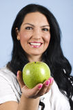Happy woman offering an apple. Happy woman offering and green apple,focus on apple,check also my collection Healthy life people Royalty Free Stock Images