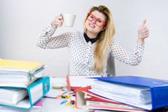 Happy woman at office drinking hot coffee Royalty Free Stock Photography