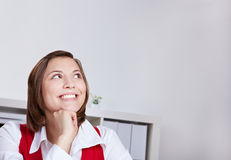Happy woman in office thinking. Happy attractive woman in office thinking and looking up Royalty Free Stock Image