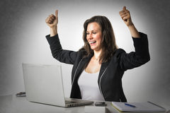 Happy woman in office with thumbs up. Happy woman sitting in office at desk in front of her laptop and holding her thumbs up Royalty Free Stock Photography