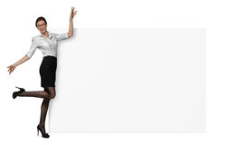 Happy woman in official clothing is holding a side of a blank banner isolated on white background Royalty Free Stock Image