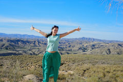 Happy woman open arms stand at mountain Royalty Free Stock Image