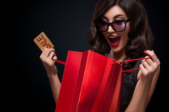 Happy woman open red bag on dark background in black friday holiday. Beautiful young woman make shopping in black friday holiday. Girl with red bag on dark royalty free stock image