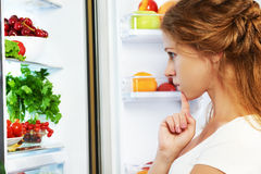 Happy woman and open refrigerator with fruits, vegetables and he Stock Image