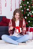 Happy woman opening christmas gift box in decorated room Royalty Free Stock Photography